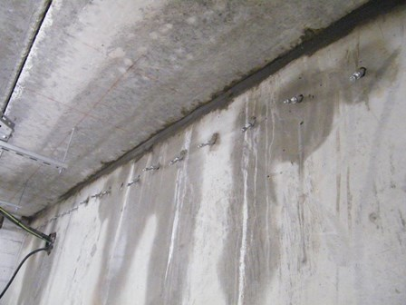 The packers were inserted into the concrete retaining wall in the basement, and resin injected into the concrete.  Seepage is already noticeably reduced, at Kells, Ballymena, Co. Antrim, Northern Ireland