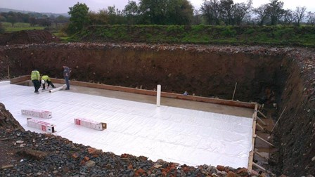 New build house & basement: membrane being rolled out onto basement slab, at Lisburn, Co. Antrim